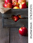 Sweet ripe apples in a rustic wooden box with heart and copy space for text. - stock photo