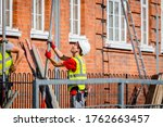 Small photo of London. UK- 06.23.2020: a man wearing safety clothing and hard helmet working as a scaffolder erecting a scaffold platform for a building.