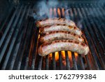 Brats Being Cooked On A Grill...