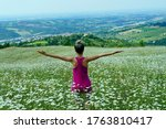 Young girl doing yoga in the daisies meadow. Meditation outdoors. - stock photo