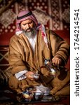 Small photo of Al Dhafra, United Arab Emirates, December 23, 2015 - An Arab Camel owner serving Arabic coffee to the guest in his tent, He is one of the camel owner exhibiting camel in Al Dhafra camel festival