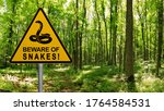 Small photo of Warning sign beware of Snakes in infested area in the green forest