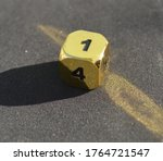 Gold metallic d6 six sided dice on foam surface in bright sunshine