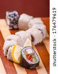 Small photo of sushi and rolls on a bamboo geta