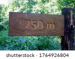 A Wooden Sign With The Distance ...