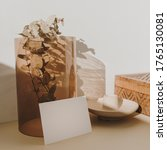 Small photo of Blank paper sheet card with mockup copy space and dry eucalyptus branch in tan glass vase in sunlight shadows on beige background. Minimal business brand template