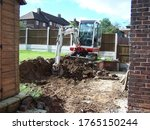 Workman Using A Mini Digger To...