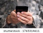 Social Cyber Warfare. Army Soldier Using Smart Phone