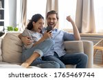 Small photo of Overjoyed surprised young couple looking at phone screen, reading message with good news, excited woman and man celebrating success, online lottery win, showing yes gesture, sitting on couch