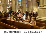 Small photo of New York, NY - June 28, 2020: A family prays during St. Patrick's Cathedral Sunday first public Mass since March when pandemic stopped large gatherings