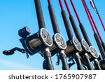 Small photo of Fishing trolling boat rods in rod holder. Big game fishing. Fishing reels and rods pattern on boat. Sea fishing rods and reels in a row
