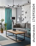 Small photo of Modern Living Room .Grey sofa and cyan blanket,carpet and curtains.Decorative honeycomb on the wall.Modern floor lamp. Design interior. Grey,white cyan colors.Closeup