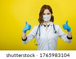 Small photo of Portrait of an optimistic female doctor insist that everything will be fine, thumb up, wear a medical mask to prevent infection with the virus, white coat.Covid19, coronavirus, healthcare and doctors