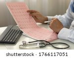 Doctor Holding Cardiogram And...