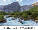 A stormy river with clear glacial water originates from the Briksdalsbreen Glacier, in Jostedalsbreen National Park, Norway. - stock photo