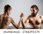 Small photo of Arm wrestling. Heavily muscled bearded man arm wrestling a puny weak man. Arms wrestling thin hand, big strong arm in studio. Two man's hands clasped arm wrestling, strong and weak, unequal match.