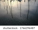 A Sahara-sand filled sky and sailboat masts reflected in water in Gulfport, Florida.