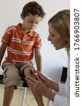 Doctor Checking Boy\'s Scraped...