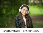 Enjoy sound music. Happy child listen to sound track in park. Small girl enjoy music playing in earphones. Hi-Fi stereo sound. New technology. Modern life. Perfect day needs perfect sound. - stock photo