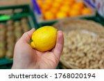 Lemon In Woman Hands On A Market