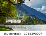 Buildings against the backdrop of Alpine mountains on the shore of lake Como in Northern Italy. Popular tourist attraction in Lombardy, Northern Italy.  - stock photo