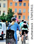 Woman with helmet biking, city apartment buildings in the background - stock photo