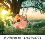 Small photo of Beautiful happy woman nymph sitting on swings. Magical fantasy swing. princess long peach color orange silk vintage dress fluttering wind. blond hair fly in motion. Tree sunshine green grass forest