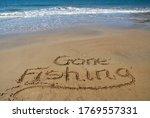 Gone Fishing Written In Sand On ...