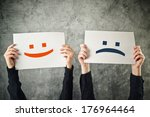 Stock photo happy and sad face emoticons two women holding papers with happiness and sadness emoji 176964464