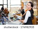 saleswoman working at cash... | Shutterstock . vector #176982935