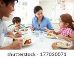 Asian Family Sitting At Table...