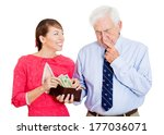 Small photo of Closeup portrait of attractive happy woman asking for money from pensive senior mature, old man hesitant to dole out dollars to her from brown wallet, isolated on white background. Negative emotions