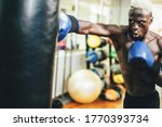 Young black man boxing inside training fitness gym club - African fit boxer doing workout session - Sport, self defense and healthy lifestyle concept - Focus on nose