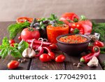 Balkan sauce ajvar and ingredients for its preparation on a wooden table. Serbian traditional food