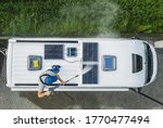 Caucasian Men in His 40s Power Pressure Washing Recreational Vehicle RV Camper Van Roof Equipped with Solar Panels. Camping Pre Season Motorhome Maintenance. - stock photo