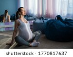Small photo of Happy pregnant woman practice yoga. A girl in the third trimester leads Pilates. Classes to prepare for childbirth. Waiting for the baby. Appeasement.