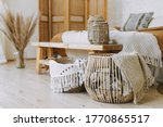 Small photo of Selective focus on home decor. Comfortable bedroom in bohemian interior style with textile sheet on bed, wooden bench seat, bamboo dressing screen, dry plants in vase, wicker basket