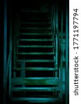 Small photo of Mystical horror staircase to a dark basement, attic in an old decrepit scary abandoned house with paranormal blue green light and terrible frightening shadows causing fear