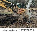 Excavator Uprooting Trees On...