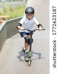 Small photo of A cute little boy rides a scooter in a skatepark. A young novice athlete spends free time in extreme sports. Lifestyle.