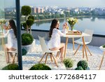 Young woman in white shirt with bare legs is enjoying sunshine at breakfast on terrace overlooking lake and city in the distance under sunny rays. On table is vase of flowers, coffee and croissants