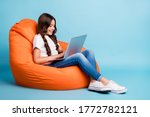 Small photo of Portrait of nice attractive lovely pretty cute focused cheerful wavy-haired girl sitting in chair using laptop isolated on bright vivid shine vibrant blue teal turquoise color background
