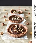 Small photo of Three chocolate tarts decorated with cream and hazelnut on baking paper abreast