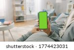 Small photo of Man at Home Lying on a Couch using Smartphone with Green Mock-up Screen, Doing Swiping, Scrolling Gestures. Guy Using Mobile Phone, Internet Social Networks Browsing. Point of View Shot.