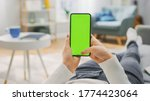 Small photo of Woman at Home Lying on a Couch using Smartphone with Green Mock-up Screen, Doing Swiping, Scrolling Gestures. Girl Using Mobile Phone, Internet Social Networks Browsing. Point of View Shot.