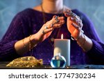 Small photo of Fortune teller woman using burning candle flame for spell, witchcraft, divination and fortune telling. Spiritual esoteric occult magic ritual illustration
