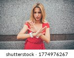 Small photo of Half length portrait of nervous female girl gesturing refuse antipathy posing at urban publicity area in city, unfriendly hipster girl dressed in polka dots apparel showing antisocial expression