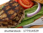 extra thick hot beef meat hamburger lunch on wooden plate with tomatoes and salad isolated on white background - stock photo