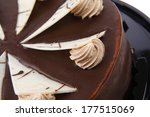 chocolate cream brownie cake topped with white chocolate slice and cream flowers on black plate isolated over white background - stock photo