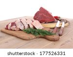 fresh raw beef meat steak and chunk with red hot pepper and dill on wooden cut plates over table - stock photo